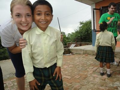 A female volunteer poses with a young student outside of a classroom in Nepal