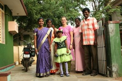A volunteer dressed in traditional clothing with her host family in their home in India