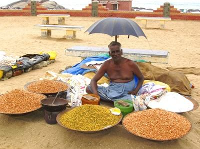 An Indian man sells a variety of foods along the road in India.