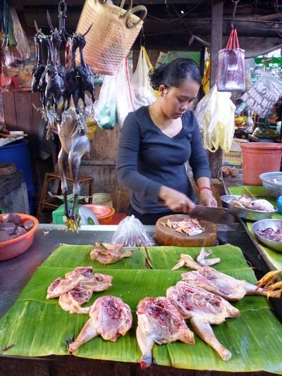 A Cambodian woman prepares food at her market stall in Cambodia, Asia.