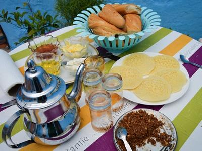 Breakfast at a Moroccan host family, with tea, almonds, crepes, honey, argan oil and baguettes