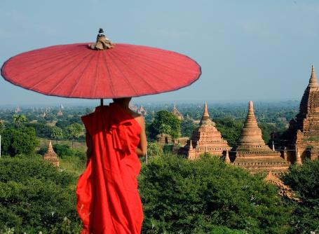 A Buddhist monk gazes over a view of ancient temples in Myanmar, also known as Burma, in Asia.
