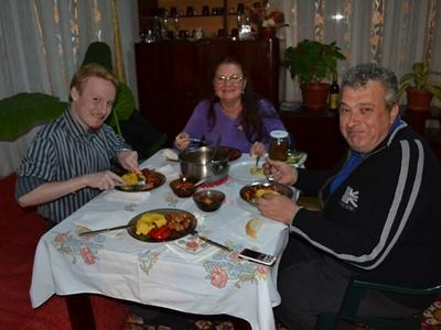 Volunteer from Denmark eats a meal with his host family in Romania