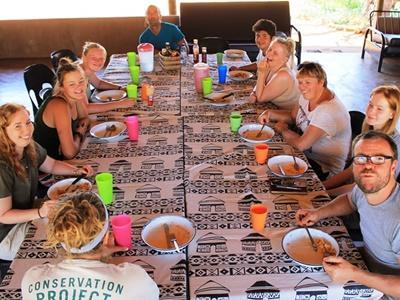 一群Projects Abroad環境保護項目義工在他們博茨瓦納的Wild at Tuli生態保護區宿舍享用飯餐