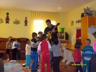 Volunteer playing the guitar for a class of children on a project in Europe