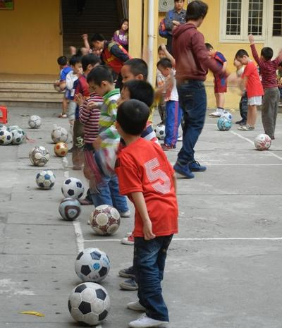 Children practicing football with their volunteer sports coach at a school in South East Asia