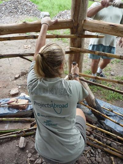 A volunteer working hard on building a wooden frame on a Building project