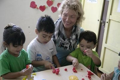 Three Costa Rican children enjoy playtime with a Projects Abroad volunteer