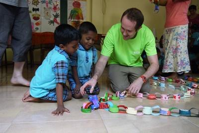 Projects Abroad Care & Community volunteer helps Sri Lankan children with an arts and crafts activity.
