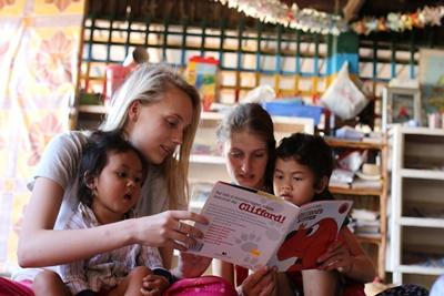 Young Care volunteers read with Cambodian children at a daycare centre in Asia.