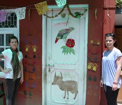 Volunteers paint a door in a facility used for the HIV/AIDS project in Nepal