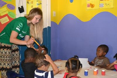 Projects Abroad Care volunteer helps a child to paint at a Jamaican day care center.
