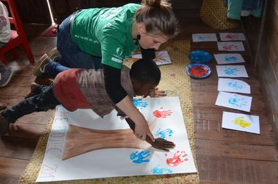 Volunteer helps a child paint a tree in a Madagascar care centre