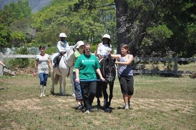 南非義工在馬術治療項目中幫助一群身心障礙兒童。