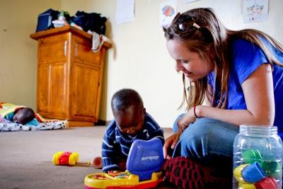 Volunteer plays with toys with orphans in an Orphanage on the Care project in South Africa