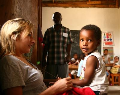 Volunteer plays with young boy in a care center in Tanzania