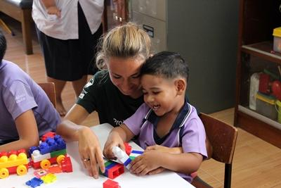 A Thai child enjoys building blocks with a volunteer at a Care placement.