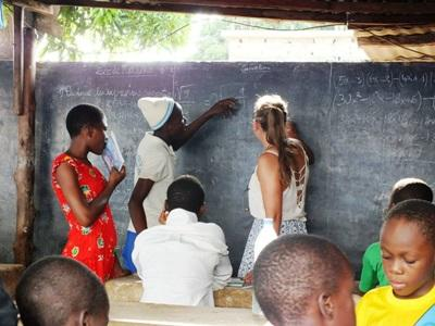 A Projects Abroad volunteer assists Togolese teenagers with homework at her care centre placement