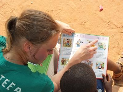 Projects Abroad volunteer reads with a Togolese child at a care centre in Lomé.