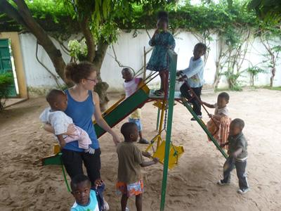 Teen volunteer plays on the playground with class of children on the Care & Community project in Togo