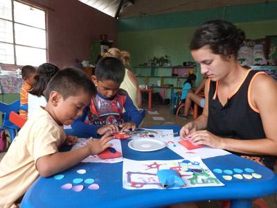 Two local children participate in a creative activity with a volunteer at a care center in Ecuador