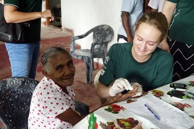 A High School Special volunteer helps check a Sri Lankan woman's blood sugar levels.