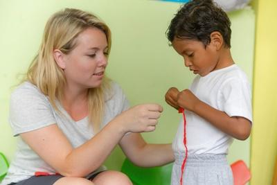 Local child gets help with an activity from a Projects Abroad Social Work intern in Ecuador.