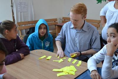 A male volunteer on the Journalism project leads an activity with children at a school in Romania.