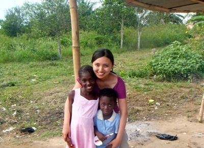 Two local girls take a picture with an Asian volunteer in Ghana