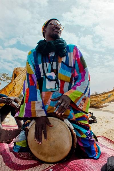 A man wearing traditional clothing plays an instrument in Senegal