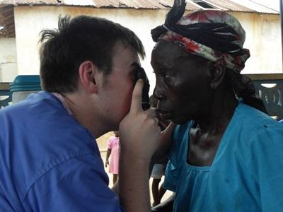 A volunteer on a medical attachment abroad performs a check-up with a local woman