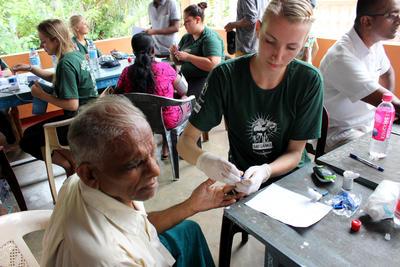 醫療外展工作,一名女義工幫一名斯里蘭卡男生量度血壓及血糖水平