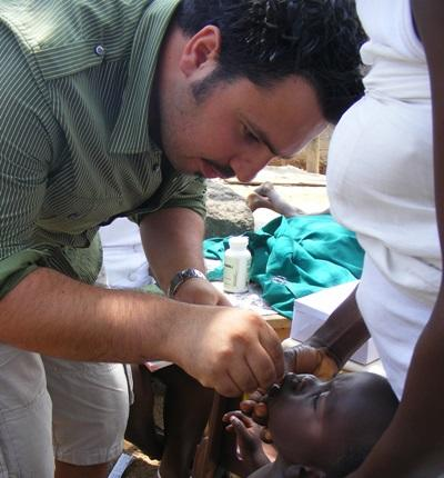Volunteer performs a dental checkup for a child in Ghana