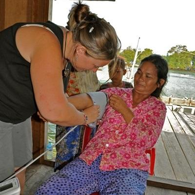 Volunteer on the Medicine project in Cambodia checking the blood pressure of a woman