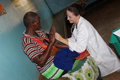 A Tanzanian woman receives help from a Projects Abroad intern on the Medicine project.