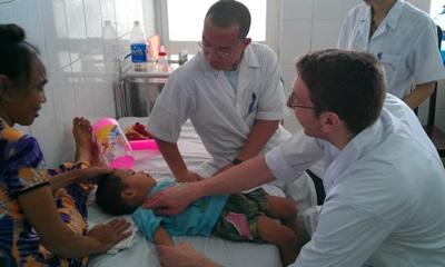A local Vietnamese doctor is assisted by a Projects Abroad medical intern