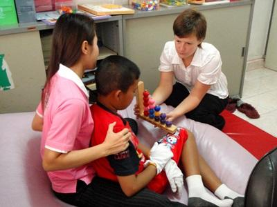Intern on the Occupational Therapy project in Cambodia does activities with children
