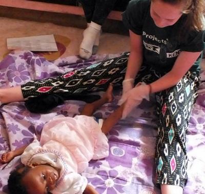 職業治療實習生在肯雅幫助一名年輕女孩活動雙腳