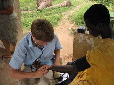 Intern on the Public Health project checks the heart rate of an older woman in Ghana