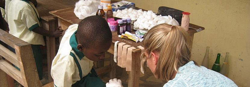 Volunteer bandaged up a young boy in an outreach project on the Public Health project