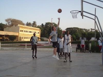 Volunteer basketball coach dunks during practice at a school in Ghana