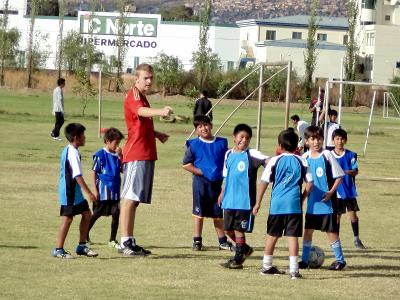 Young Bolivian children enjoy a football lesson with a Projects Abroad volunteer