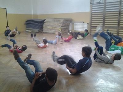 Romanian children participate in warm-up exercises with a male volunteer