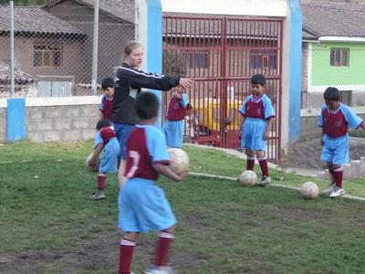 Volunteer soccer coach instructs children at a school in Peru