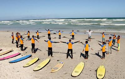 Disadvantaged children stretch alongside Surfing volunteers in Cape Town, South Africa