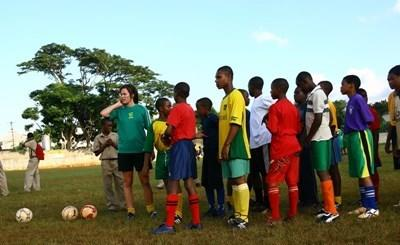 Sports volunteer coaches students at a school in Jamaica