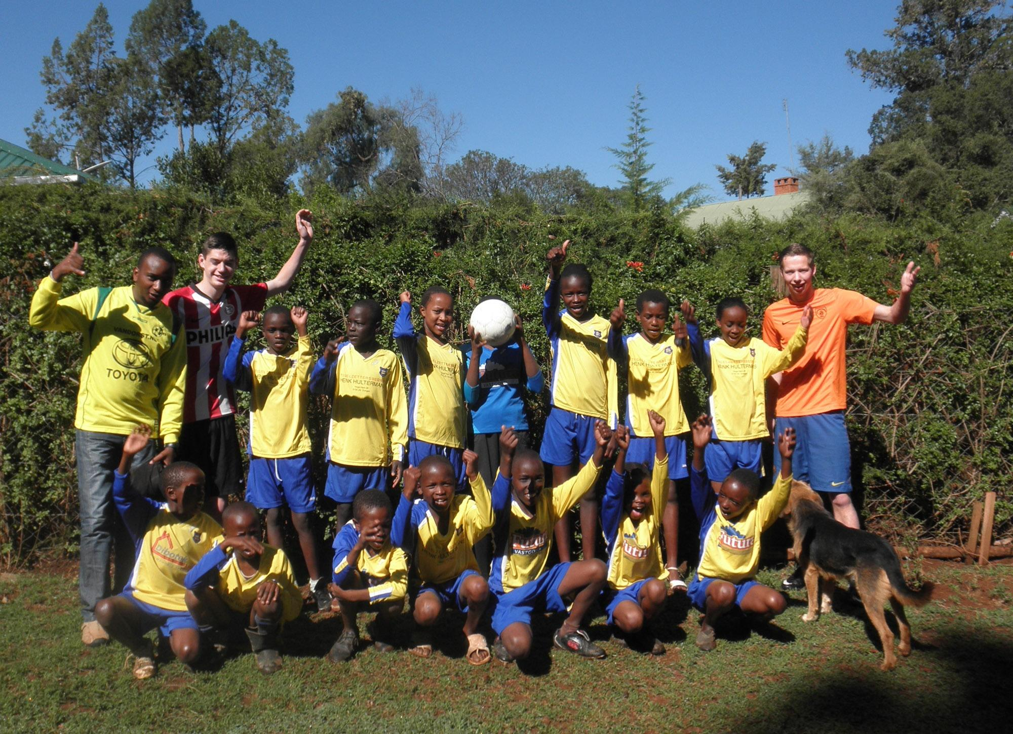 Young members of the school soccer team pose for a picture with volunteers.