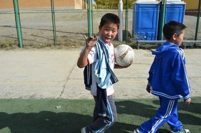 蒙古男童在義工指導下練習踢足球技巧