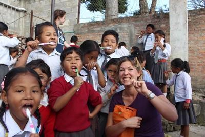 A female UK volunteer teaches Nepalese children about hygiene