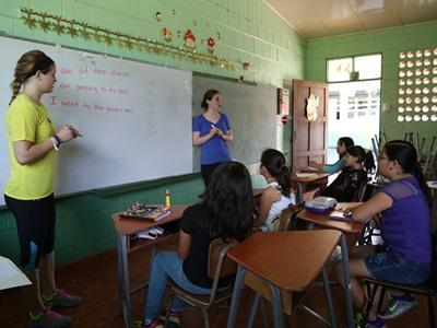 A group of Costa Rican school children listen to two Projects Abroad volunteers during class
